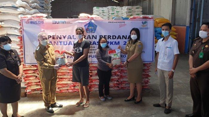 Penyerahan bantuan beras PPKM secara simbolis oleh Bupati Evangelian Sasingen kepada perwakilan KPM.