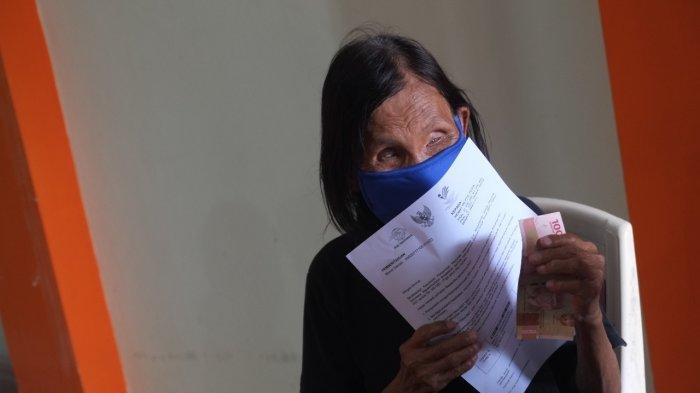 Petugas melakukan verifikasi visual penerima manfaat di Kantor Pos, Manado, Sulawesi Utara, Senin (26/7/2021).
