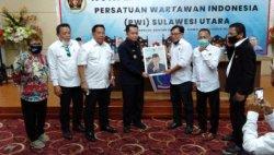 Pjs Gubernur Sulut, Agus Fatoni diberikan bingkisan berupa lukisan wajah sang pemimpin oleh Ketua Panitia Aswin Lumintang didampingi Ketua PWI Sulut, Voucke Lontaan.
