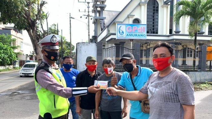 Polisi Bagi Vitamin dan Masker kepada Warga Minsel