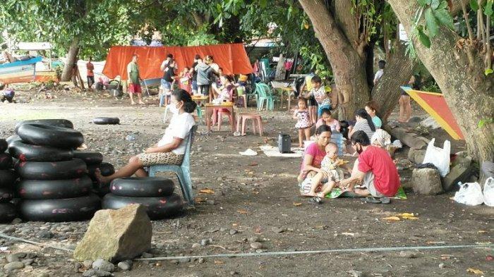 Puluhan warga berwisata di Pantai malalayang di saat weekend usai perayaan Idul Fitri, Minggu (16/5/2021). Libur panjang membuat warga antusias dalam mengunjungi objek-objek wisata.
