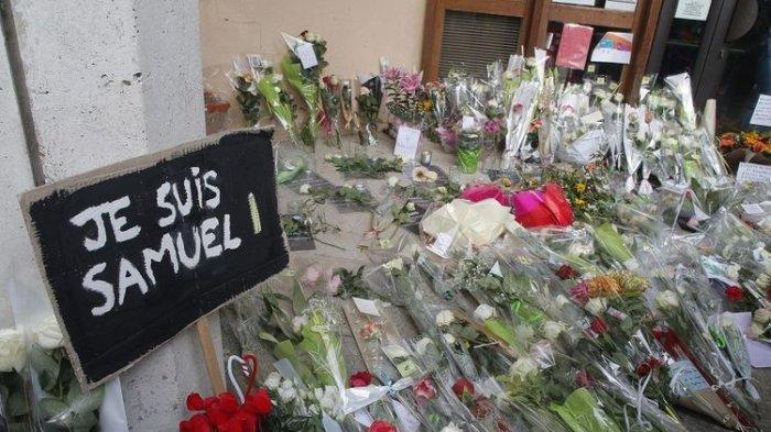 Sebuah poster bertuliskan Saya Samuel dan bunga-bunga tergeletak di luar sekolah tempat guru sejarah yang terbunuh, Samuel Paty, bekerja, Sabtu, 17 Oktober 2020 di Conflans-Sainte-Honorine, barat laut Paris.