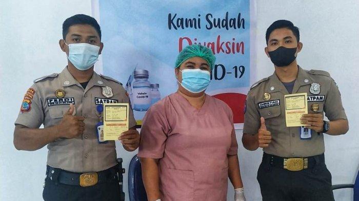 Security Bank KMC Manado menunjukkan kartu Vaksinasi dan Petugas Puskesmas Covid-19 foto bersama