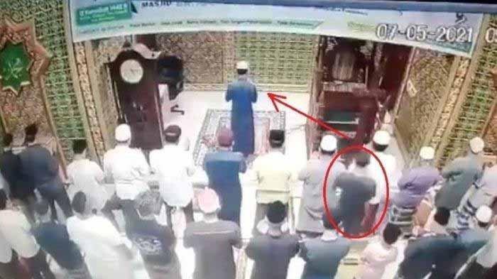 Seorang pria bercelana pendek dan pakai kaus hitam tiba-tiba menghampiri Imam Masjid di Pekanbaru lalu memukulinya.