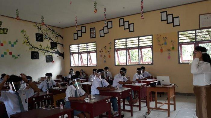 SMA Negeri 1 Lobbo Gelar KBM Pertama di Talaud di Masa Pandemi Covid-19 - situasi-dalam-kelas-guru-mengarahkan-pemakaian-masker-dan-face-shield-yang-benar.jpg