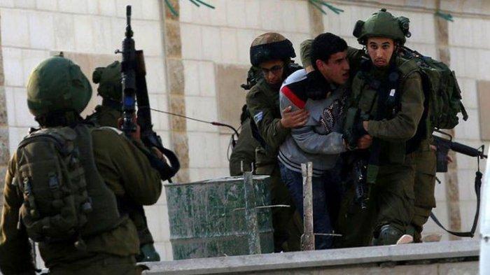 Tentara Israel menahan seorang Palestina yang melakukan aksi protes di Tepi Barat, Desember 2017 lalu.