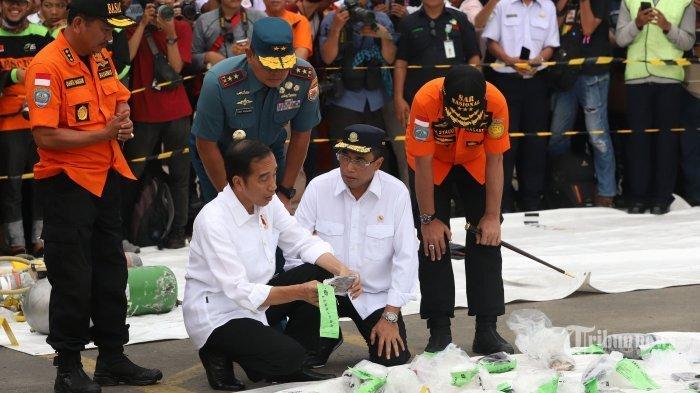 Presiden Joko Widodo terlihat tertunduk dan memandangi deretan barang milik korban Pesawat Lion Air JT 610 di Posko SAR Dermaga JICT Tanjung Priok