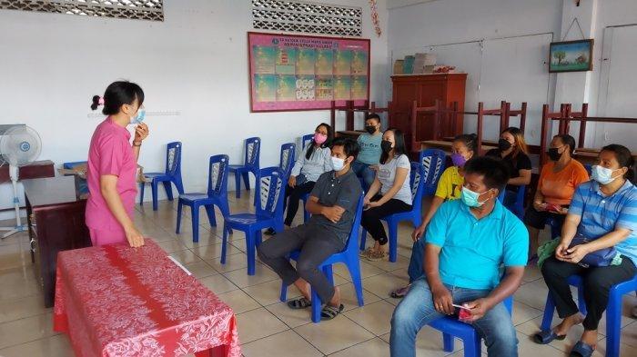 Petugas kesehatan di Kota Bitung memberi arahan kepada warga sebelum menjalani vaksinasi Covid-19, Senin (21/6/2021).