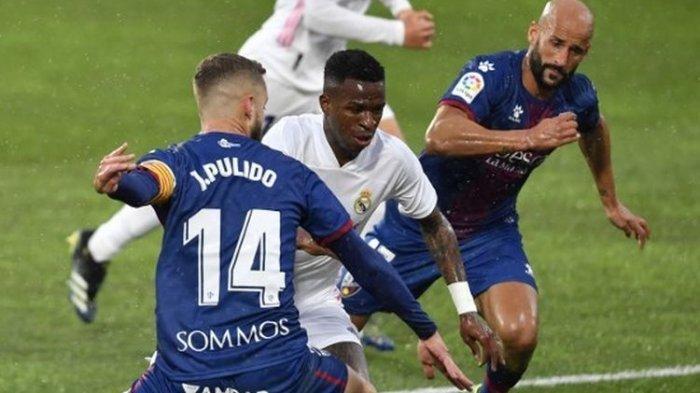 Penyerang muda Real Madrid, Vinicius Junior (tengah), mencoba melewati para pemain Huesca, Sabtu (6/2/2021) malam WIB di Stadion El Alcoraz.