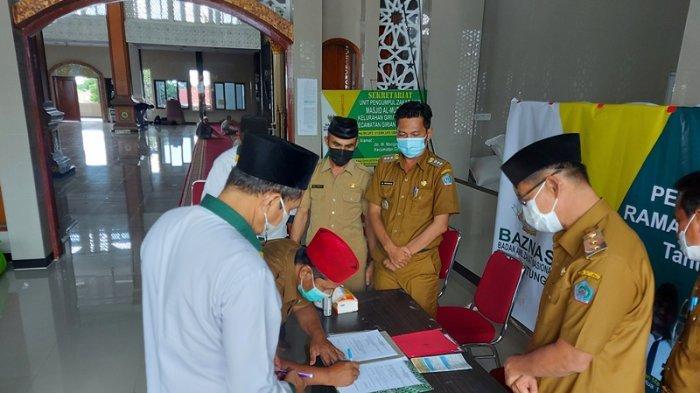 Wakil wali kota Bitung menyerahkan simbolis paket sembako kepada Unit pengumpul zakat (UPZ).