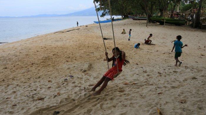 Warga bersantai di tepi Pantai Kinunang, Desa Kinunang, Kecamatan Likupang, Kabupaten Minahasa Utara, Rabu (25/8/2021).