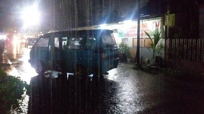 Warga Kelurahan Banjer Lingkungan 1, Tikala, Manado, Sulawesi Utara mengalihkan arus lalu lintas karena terjadi banjir, Jumat (16/7/2021).