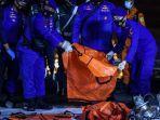 anggota-kepolisian-mengangkat-kantong-jenazah-berisi-objek-temuan.jpg