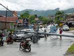 foto-warga-melintasi-tiang-listrik-melintang-di-jalan-roboh-karena-gempa-bumi-di-mamuju-sulbar.jpg