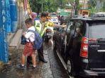 kapolresta-manado-kombes-pol-benny-bawensel-saat-membantu-salah-satu-siswa-untuk-turun-dari-mobil.jpg