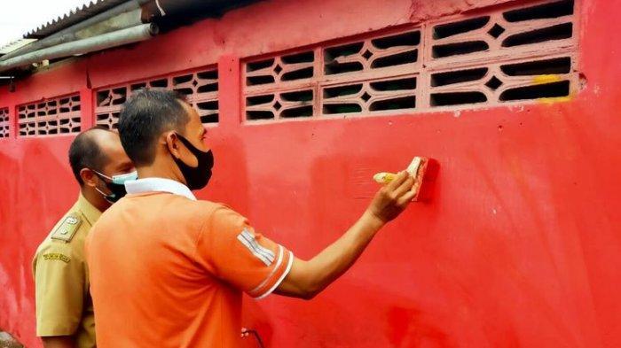 Aparat kelurahan Sentul, Kecamatan Kepanjenkidul, Kota Blitar menghapus mural dan coretan bernada kritikan kepada pemerintah di sebuah bidang tembok di Jalan Moh Hatta menjelang kedatangan Presiden Jokowi, Selasa (7/9/2021)