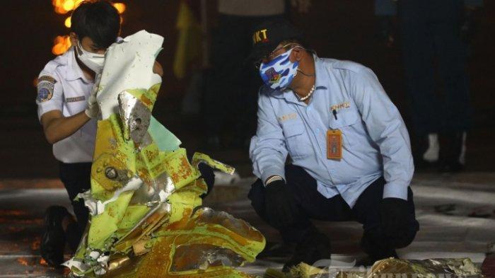 Anggota Komite Nasional Keselamatan Transportasi (KNKT) memeriksa bagian pesawat Sriwijaya Air SJ182 rute Jakarta - Pontianak yang jatuh di perairan Pulau Seribu di Dermaga JICT, Tanjung Priok, Jakarta Utara, Minggu (10/1/2021). Temuan bagian pesawat selanjutnya akan diperiksa oleh KNKT sedangkan potongan tubuh korban diserahkan kepada DVI Polri untuk identifikasi lebih lanjut.