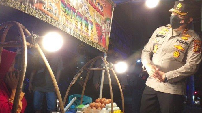 Kapolda Riau Irjen Pol Agung Setya Imam Effendi saat memborong semua kerak telor yang dijual Yanti (58), di pinggir Jalan Imam Munandar, Kota Pekanbaru, Riau, Jumat (23/7/2021) malam.