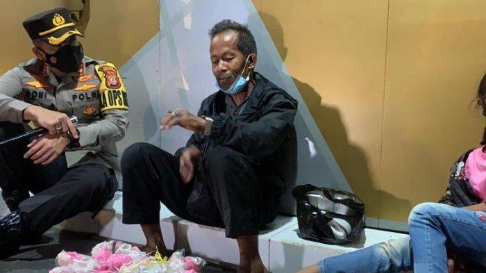 Kepala Polresta Tasikmalaya AKBP Doni Hermawan, membangunkan tukang kerupuk keliling yang tertidur kelelahan bersama anak perempuannya asal Ciamis, untuk diberi uang Rp 300.000 sekaligus memborong dagangannya di Jalan Mitra Batik, Kota Tasikmalaya, Sabtu (24/7/2021) dini hari.