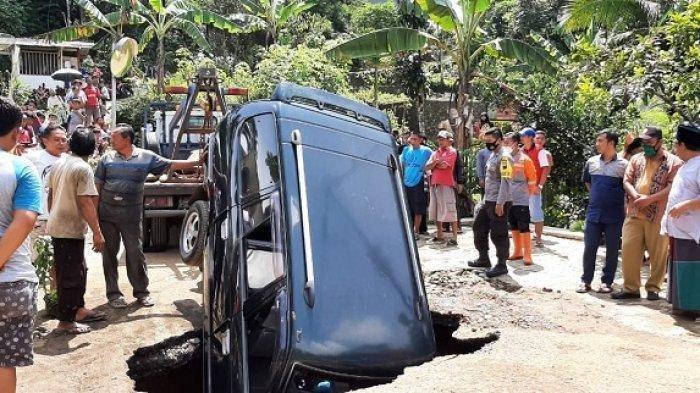 Mobil Kijang terperosok ke dalam lubang di Jalan Kaliwiro Wonosobo, Selasa (16/2/2021).