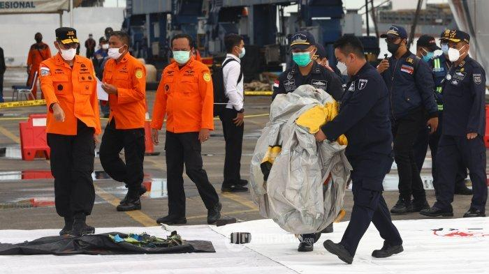 Petugas gabungan memeriksa benda yang diduga serpihan dari pesawat Sriwijaya Air SJ 182 rute Jakarta - Pontianak yang hilang kontak di perairan Pulau Seribu, di Dermaga JICT, Jakarta, Minggu (10/1/2021). Pesawat Sriwijaya Air SJ 182 yang hilang kontak pada Sabtu (9/1) sekitar pukul 14.40 WIB di ketinggian 10 ribu kaki tersebut membawa enam awak dan 56 penumpang.