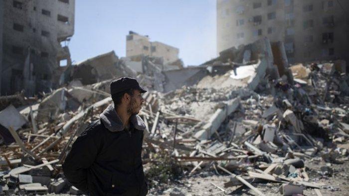 Seorang polisi Palestina berdiri di depan reruntuhan Jala Tower, gedung 13 lantai kantor media Al Jazeera dan Associated Press, yang diledakkan serangan udara Israel di Gaza pada Sabtu (15/5/2021).