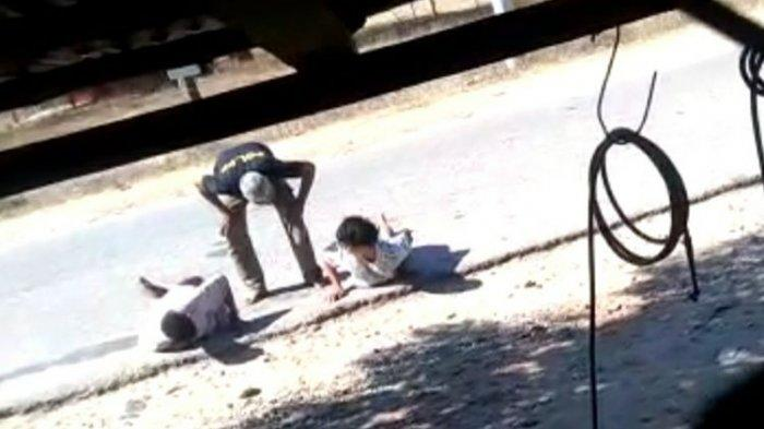 Tampak pria yang memakai baju kaos yang bertuliskan Pol PP (tunduk) sedang menginterogasi dua warga di pinggir jalan.
