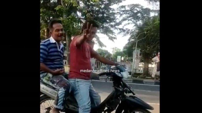 Tangkapan layar video unggahan akun Instagram @medanheadlines.news yang memperlihatkan pelaku pemalakan mengacungkan dua jari bertanda V. Pelaku memalak pedagang buah di Jalan Gatot Subroto pada Sabtu (4/9/2021) yang sedang sepi jualannya.