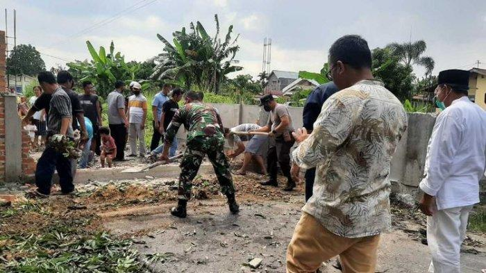 Warga bersama kepolisian dan TNI membongkar tembok batu bata yang dipasang Nur Sayuti untuk menutup jalan di Kelurahan Perhentian Marpoyan, Kecamatan Marpoyan Damai, Kota Pekanbaru, Riau, Jumat (16/4/2021).