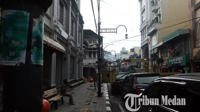Pekerja dari Dinas Kebersihan dan Pertamanan Kota Medan melakukan pengecatan tiang lampu di Jalan Ahmad Yani, Medan, Selasa (6/4/2021). Pengecatan tersebut upaya mempercatik dan juga perawatan tiang lampu penerangan di kawasan City Walk Medan.