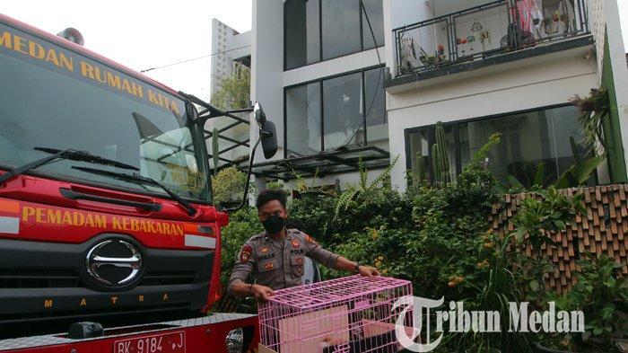 Petugas kepolisian membantu mengevakuasi barang korban kebakaran di di Perumahan Bumi Asri, Medan, Senin (7/6/2021). Tidak ada korban jiwa dalam musibah tersebut, diduga api berasal dari korsleting listrik.