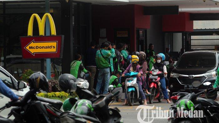 Antrean driver ojol dan warga di salah satu gerai McDonald's di Ringroad, Medan, Rabu (9/6/2021). Dampak adanya promo paket BTS Meal, mengakibatkan terjadinya penumpukan warga sehingga melanggar protokol kesehatan pencegahan Covid-19.