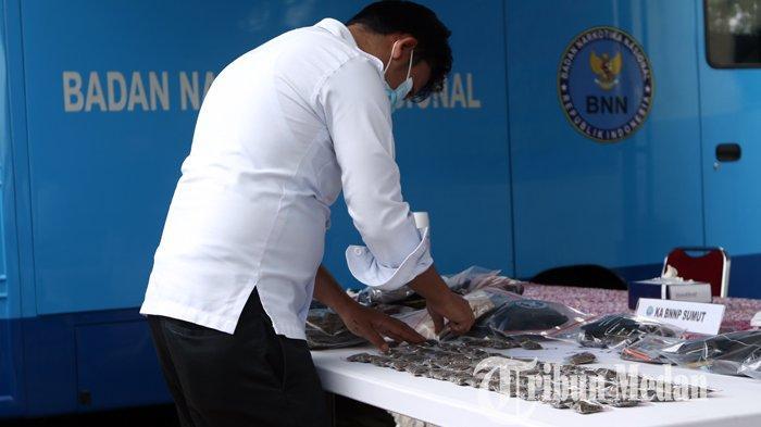 Petugas BNNP Sumut menyusun barang bukti narkoba saat gelar kasus di kantor BNNP Sumut, Deliserdang, Senin (11/10/2021). BBNP Sumut melakukan kerja sama dengan pihak Universitas Sumatera Utara (USU) berhasil menangkap 31 orang pengguna narkoba, 14 orang diantaranya mahasiswa dan mengamankan barang bukti ganja kering seberat 508,6 gram.