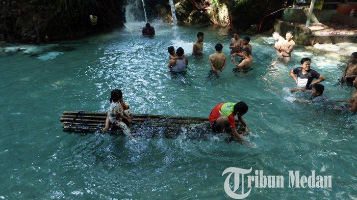 Sejumlah wisatawan menikmati suasana objek wisata Pemandian Bah Damanik, Simalungun, Minggu (14/2/2021). Wisata pemandian tersebut menjadi salah satu pilihan utama masyarakat untuk memanfaatkan liburan Imlek.