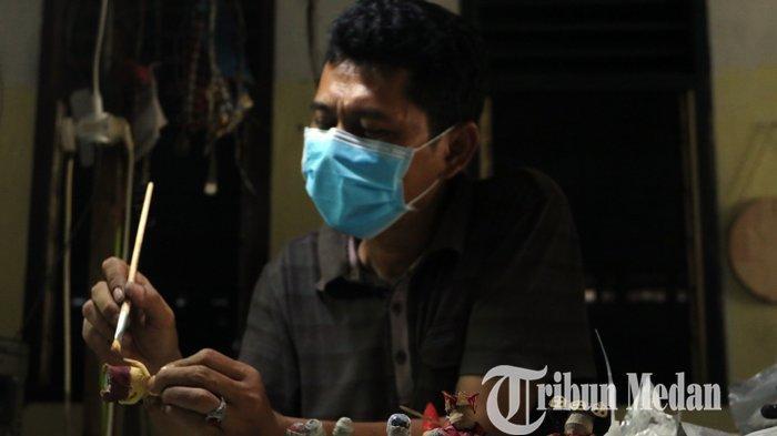 Faisal Walad menyelesaikan kerajinan miniatur boneka berpakaian adat multi etnis berbahan koran bekas di Galeri J-ART, di Jalan Umar, Medan, Selasa (16/2/2021). Kerajinan tersebut guna melestarikan sekaligus mempromosikan tujuh pakaian adat di Sumatera Utara, dijual dengan harga Rp 150.000 per pasang.
