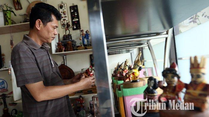 Faisal Walad menyusun miniatur boneka berpakaian adat multi etnis berbahan koran bekas hasil kerajinannya di Galeri J-ART, di Jalan Umar, Medan, Selasa (16/2/2021). Kerajinan tersebut guna melestarikan sekaligus mempromosikan tujuh pakaian adat di Sumatera Utara, dijual dengan harga Rp 150.000 per pasang.