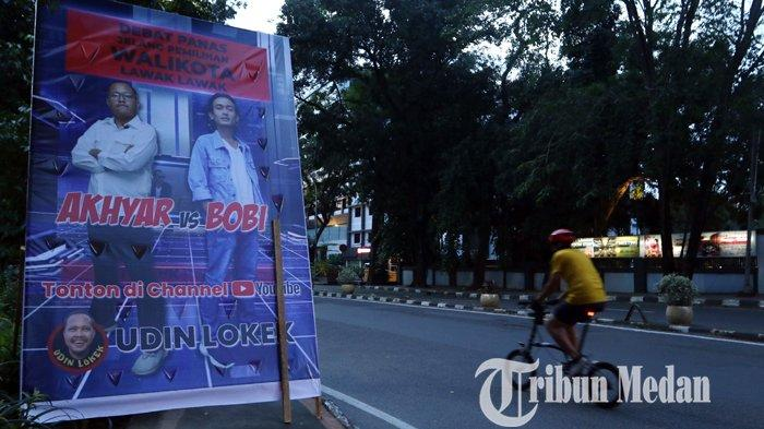 Pengendara melintas tepat di samping baliho unik Debat Panas Pilkada 2020 yang terpasang di Jalan Sudirman, Medan, Sabtu (21/11/2020). Baliho yang bertuliskan Debat Panas Jelang Pilkada Lawak-lawak, dengan dua sosok yang bernama Akhyar dan Bobi.