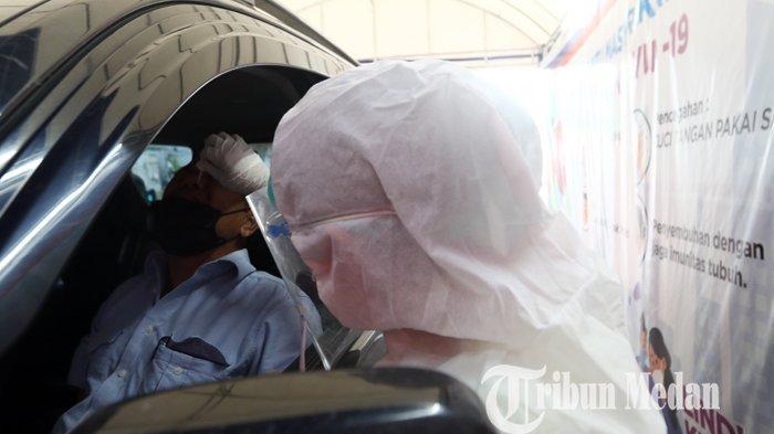 Petugas kesehatan melakukan pengecekan kepada pengguna kendaraan saat Rapid Test Antigen Covid-19 dengan sistem drive thru di kawasan Lapangan Merdeka, Medan, Selasa (23/3/2021). Tes dengan sistem tersebut dilakukan guna mempercepat proses pemeriksaan dan mempersempit penyebaran penularan Covid-19 di wilayah Kota Medan.