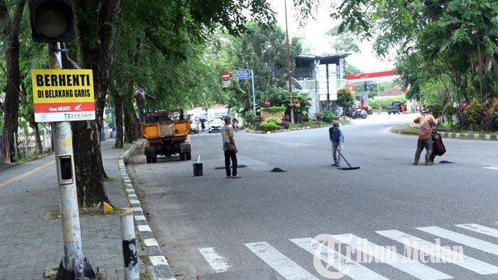 Pekerja menyelesaikan pengerjaan tambal sulam aspal yang berlubang di Jalan Sudirman, Medan, Selasa (26/1/2021). Perbaikan jalan secara tambal sulam tersebut dilakukan guna mengatasi jalan berlubang, demi kenyamanan para pengendara.