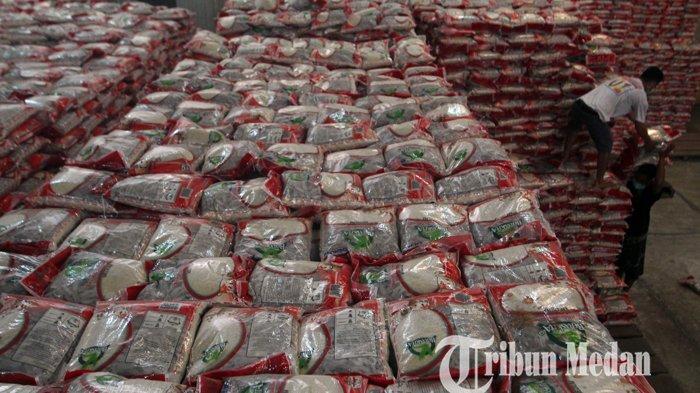 Pekerja mengangkut beras kedalam truk untuk disalurkan ke masyarakat yang terdampak PPKM, di Gudang Perum Bulog Kantor Wilayah Sumatera Utara, di Jalan Jemadi, Medan, Senin (26/7/2021). Bulog Sumut menyalurkan beras Bansos PPKM sebanyak 9.525.310 kilogram untuk 952.531 Keluarga Penerima Manfaat (KPM).