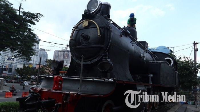 Pekerja membersihkan monumen lokomotif kereta api tua di Jalan Stasiun, Medan, Kamis (26/12/2019). Monumen lokomotif tersebut merupakan benda heritage yang harus terjaga kelestariannya, dan menjadi sejarah perkereta apian di Kota Medan.
