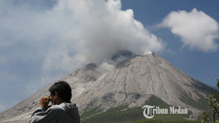 Asap sulfatara mengepul disertai guguran material vulkanik dari puncak Gunung Sinabung dari Desa Sigarang-garang, Kecamatan Namanteran, Karo, Sumatera Utara, Sabtu (21/2/2021).TRIBUN MEDAN/RISKI CAHYADI