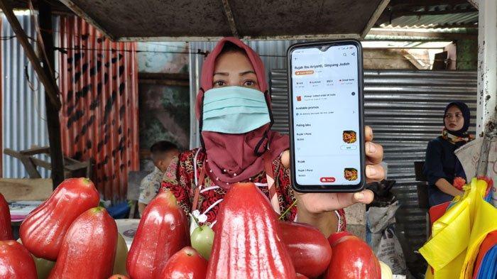 Ariyanti, penjual Rujak di Simpang Jodoh saat menunjukkan aplikasi Gofood di telepon genggam nya, Sabtu (24/10/2020). Selama masa pandemi, dagangan Rujak milik Ariyanti  sangat terbantu melalui pesanan via Gofood.
