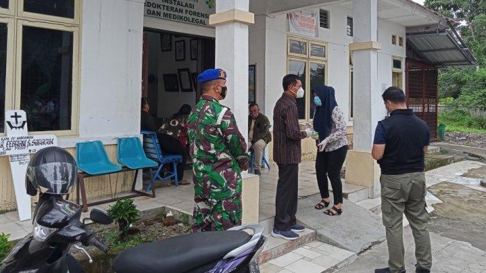 Bupati Simalungun JR Saragih menantikan proses pembersihan jenazah seorang karyawannya  di ruang instalasi jenazah RSUD Djasamen Saragih Pematangsiantar, Selasa (6/10/2020) siang