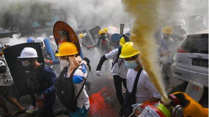 Para Demonstran berlari menggunakan pemadam api sebagai perisai buatan di Yangon.