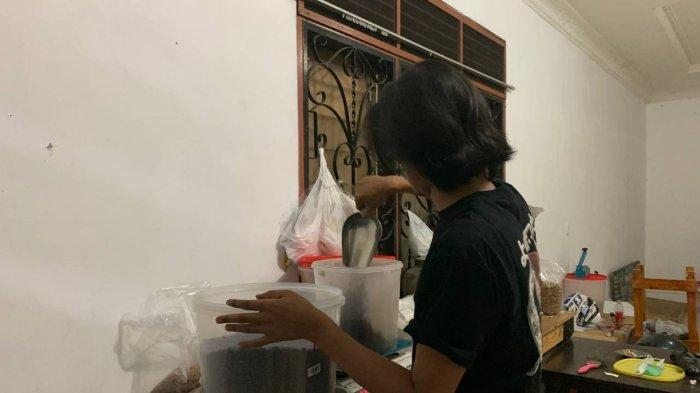 Dirwan Doni (Baju hitam) sedang melakukan proses menggiling biji kopi menjadi bubuk.