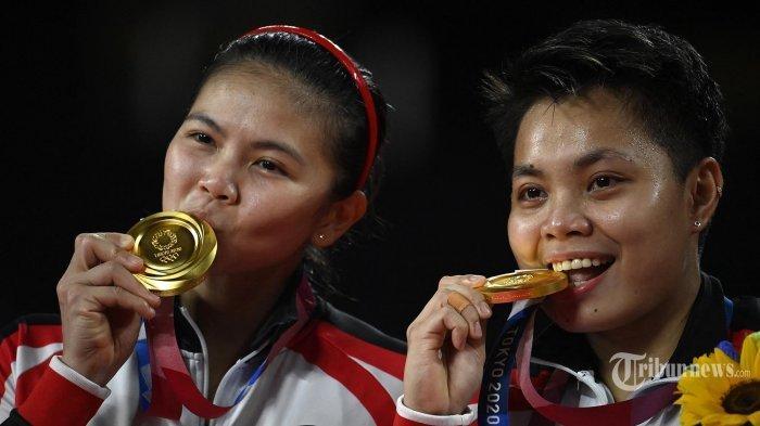 Atlet Indonesia Apriyani Rahayu (kanan) dan Greysia Polii Indonesia berpose dengan medali emas bulu tangkis ganda putri mereka pada upacara selama Olimpiade Tokyo 2020 di Musashino Forest Sports Plaza di Tokyo pada 2 Agustus 2021.