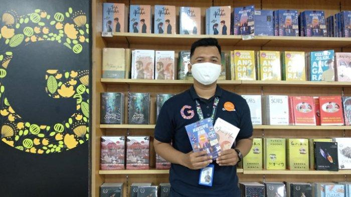 Sales Superintendent Gramedia Gajah Mada Medan Rio Dermawan Syahputra menunjukkan buku saat ditemui Tribun Medan di Gramedia Gajah Mada Medan, Kamis (23/7/2020). Gramedia PayDay kembali hadir dengan diskon sebesar 30% dan berlaku untuk seluruh buku.