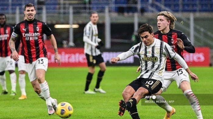 Penyerang Juventus asal Argentina Paulo Dybala menendang bola di bawah tekanan dari penyerang Norwegia AC Milan Jens Petter Hauge (kanan) selama pertandingan sepak bola Serie A Italia AC Milan vs Juventus pada 6 Januari 2021 di stadion San Siro di Milan.