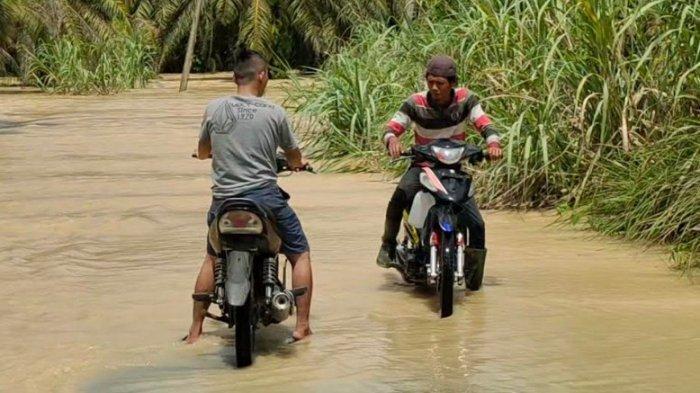 Kondisi jalan yang terputus akibat banjir luapan sungai Sakur di Kecamatan Rahuning yang mengakibatkan perekonomian warga desa Gunung Melayu terganggu, Jumat(2/7/2021). (TRIBUN MEDAN/ALIF)